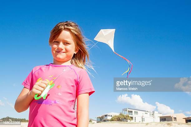 Young Girl Flying Handmade Kite on Beach