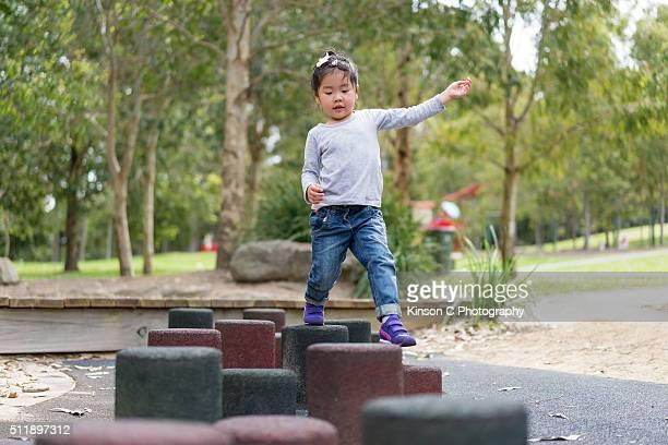 Young Girl Focusing Whilst Walking On Balancing Blocks At Park