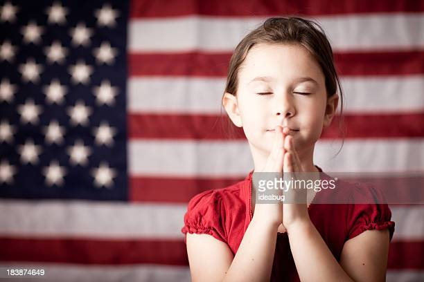 Young Girl Folding Hands and Praying by American Flag