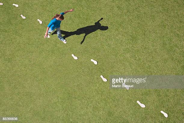 young girl following footprints on grass - following stock pictures, royalty-free photos & images
