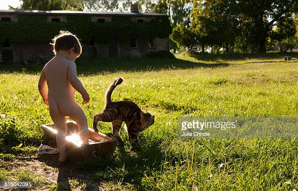 A young girl following her cat through a trough with water in it
