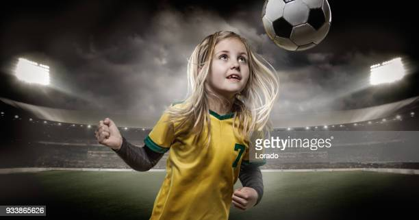Young girl football player heading a soccer ball in a floodlit stadium