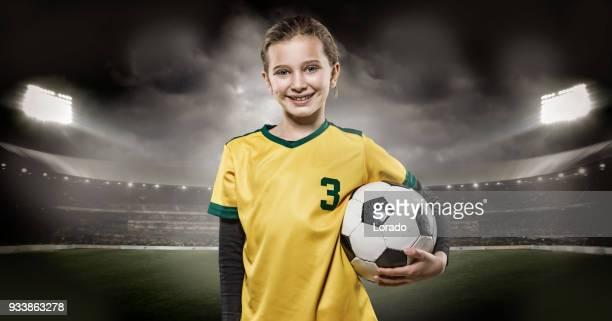 young girl football player holding a soccer ball in a floodlit stadium - sports team event stock photos and pictures