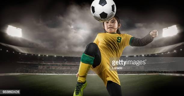 futbolista joven pateando un balón de fútbol en un estadio con iluminación - sports team event fotografías e imágenes de stock