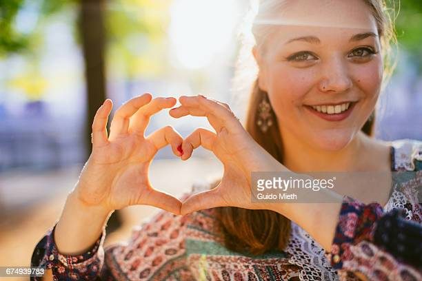 Young girl forming a heart with hands.
