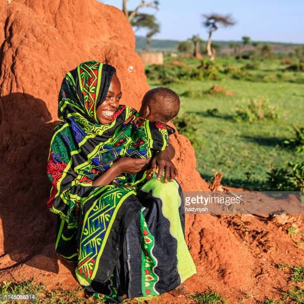 young girl from borana tribe holding baby, ethiopia, africa - african tribal culture stock pictures, royalty-free photos & images