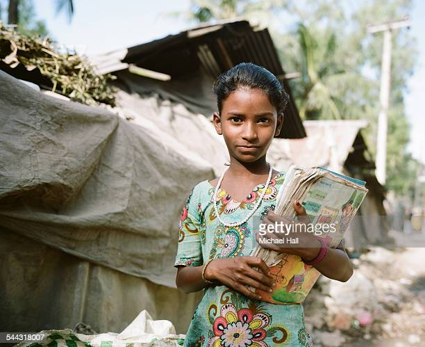 Young girl from slum with school books