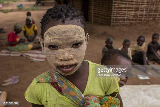 Young girl from the Makonde ethnic group wearing earth makeup on her facen, a beauty symbol, carries a baby on her back as she poses for pictures in...