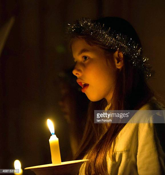 Young girl from the Sankta Lucia festival of light choir holds a candle as she prepares to take part in the procession at York Minster on December...
