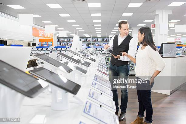 young girl gets information about new products - electronics store stock photos and pictures