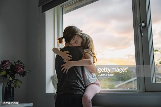 young girl getting a big cuddle from her mother - embracing stock pictures, royalty-free photos & images