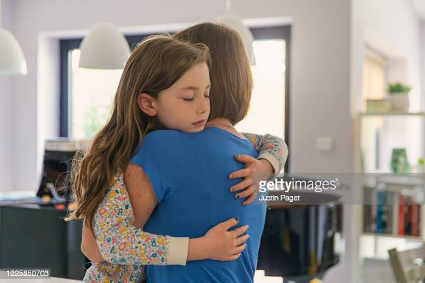 young girl getting a big cuddle from her mum - single mother stock pictures, royalty-free photos & images