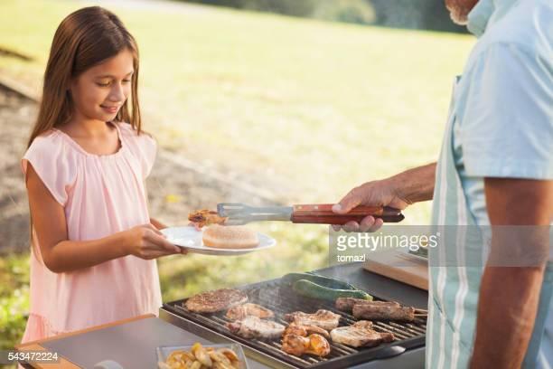 Chica joven conseguir que su carne de barbacoa.