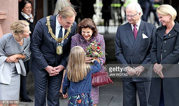 A young girl gives flowers to the Queen Silvia of Sweden next to King Carl Gustav of Sweden swedish social Minister Aasa regner Leipzig's Mayor...