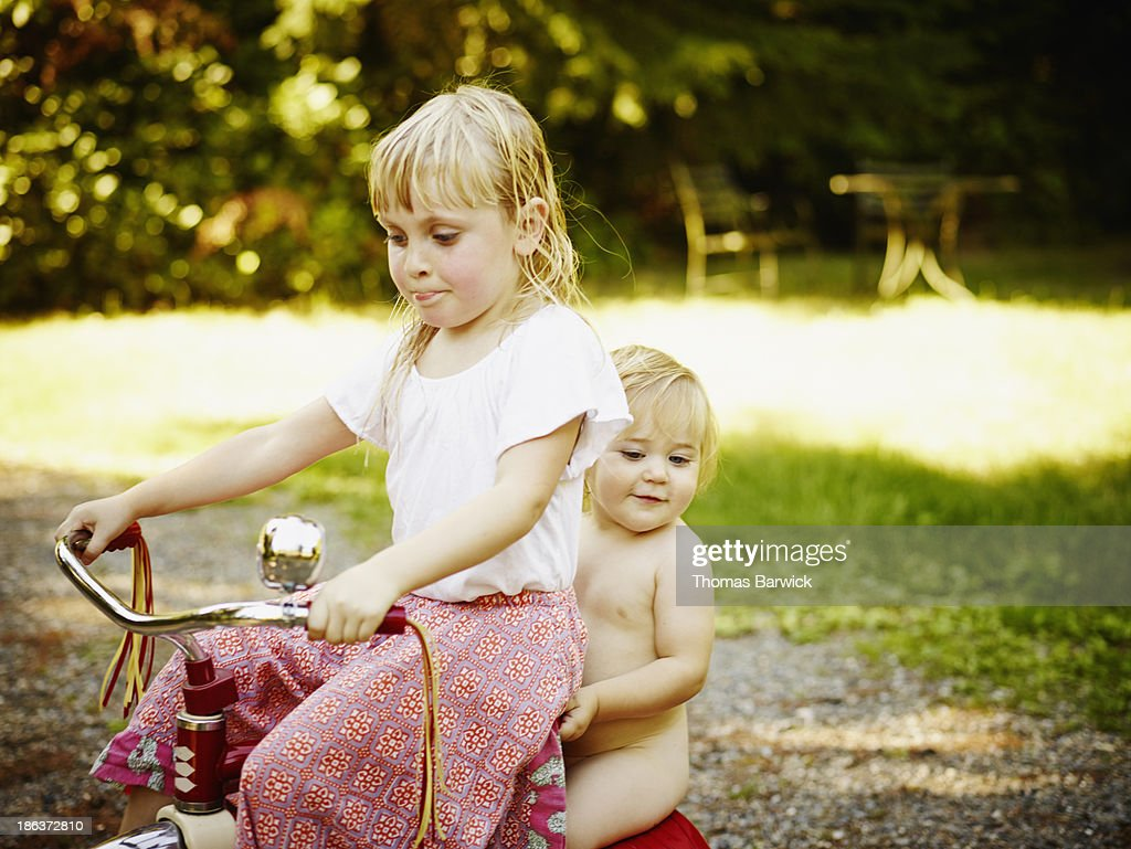 Young girl giving baby sister a ride on tricycle : Stock Photo