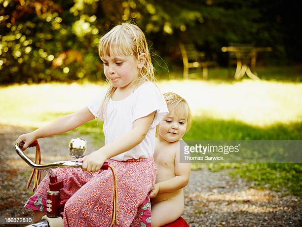 Young girl giving baby sister a ride on tricycle