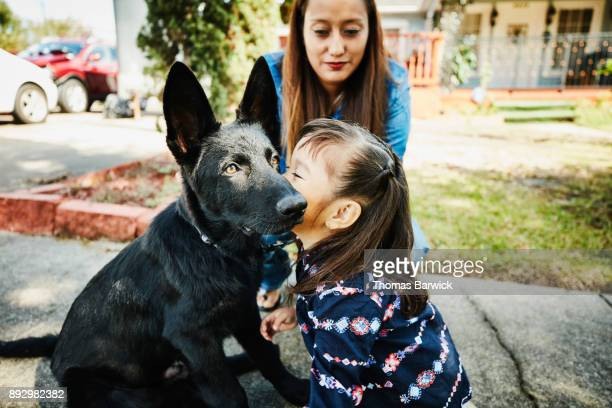Young girl giving her dog a kiss