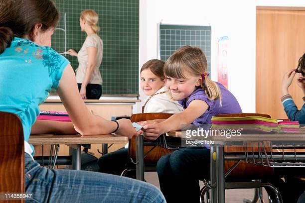 young girl giving little note to friend in classroom - gruppo medio di persone foto e immagini stock