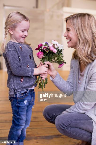 Young girl giving mother bunch of flowers