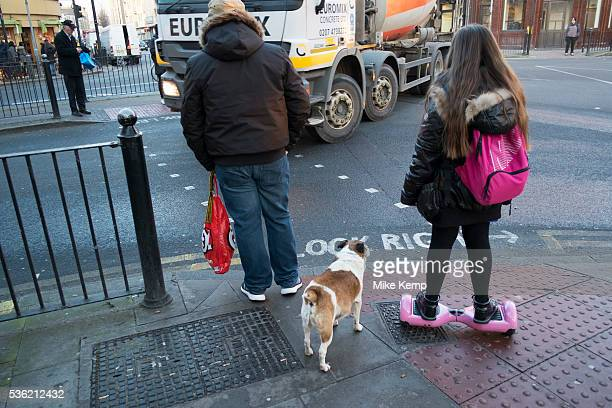 Young girl going home from school on her hoverboard accompanied by a guardian and her dog Hackney London England UK A selfbalancing twowheeled board...