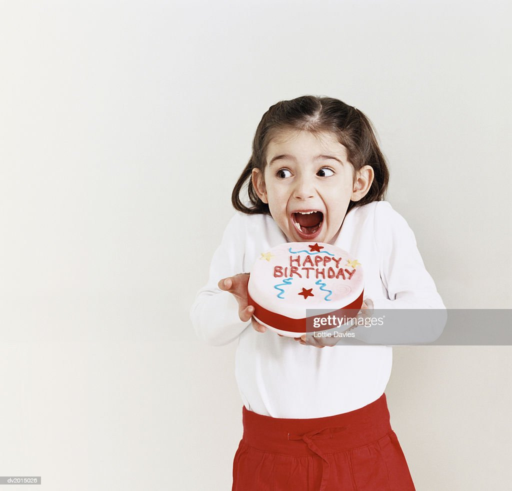 Young Girl Greedily Eating a Birthday Cake : Stock Photo
