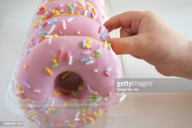 Young Girl Hand Grabbing a Sweet Sweet Pink Doughnuts Confection