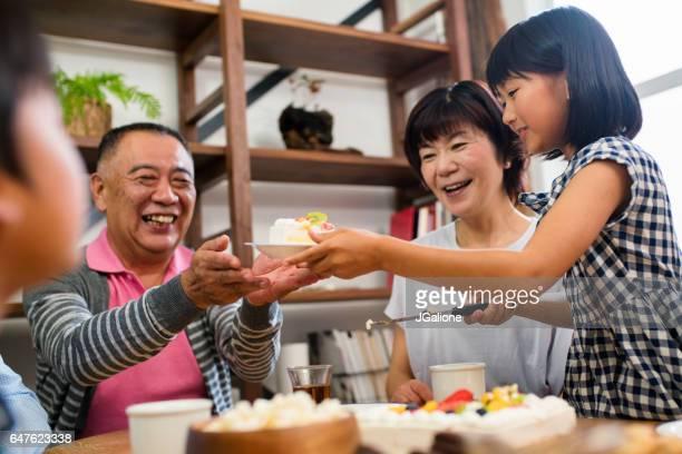 若い女の子が彼女の祖父に誕生日ケーキを渡す