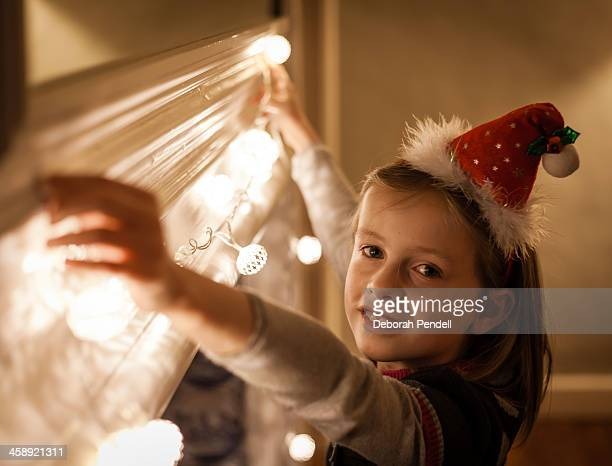 Young girl hanging Christmas fairy lights