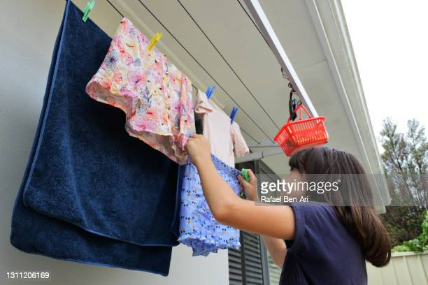 young girl hanging laundry on washing line - rafael ben ari stock pictures, royalty-free photos & images