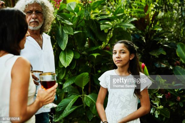 Young girl hanging out with family during backyard dinner party
