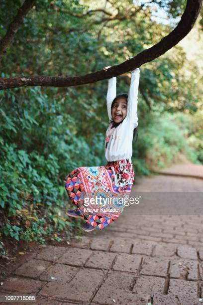 young girl (4-5 years) hanging to the tree trunk - 4 5 years stock pictures, royalty-free photos & images