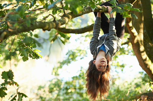 Young girl hanging upside down branch - gettyimageskorea