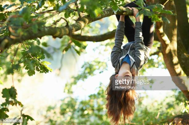young girl hanging upside down branch - jouer photos et images de collection