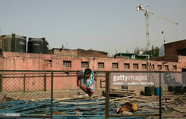 A young girl hangs from cloth on a fence next to a construction site near a slum on June 7 in New Delhi India Inadequate access to safe water...