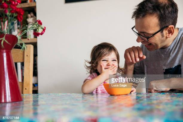 a young girl happily enjoying snack time with her dad - toddler stock pictures, royalty-free photos & images
