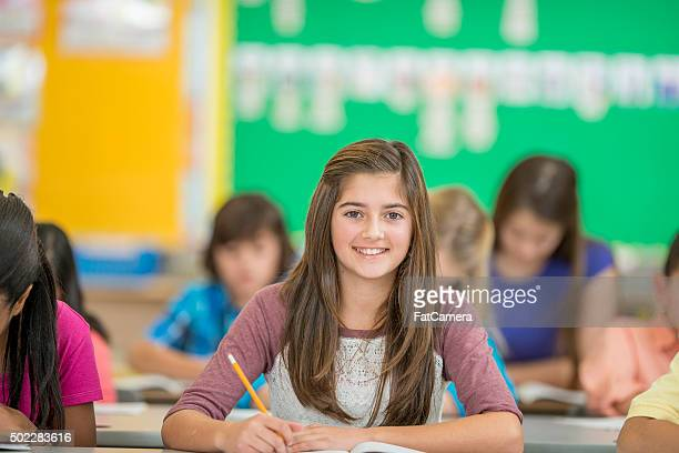 Young Girl Happily Sitting in Class