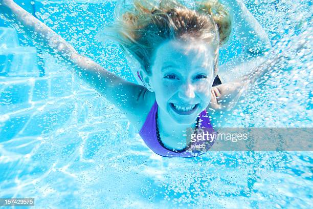A young girl happily swimming in a pool