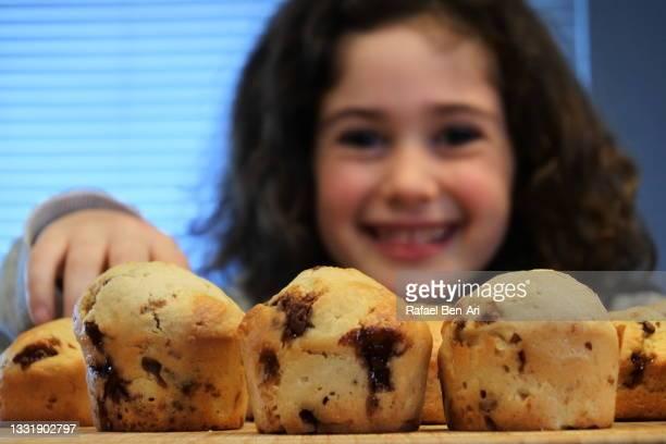 young girl happy to eat fresh baked chocolate muffins - rafael ben ari stock-fotos und bilder