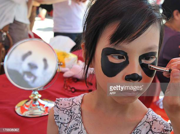 A young girl has her face painted with a panda pattern as Taipei City Zoo held a 'babyshower' party to celebrate the onemonth birthday of the panda...