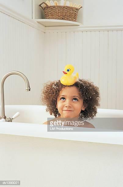 young girl having a bath looking up at a rubber duck on her head - menina infancia pelada banheira imagens e fotografias de stock