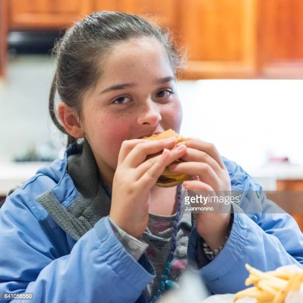 Young girl having a hamburger