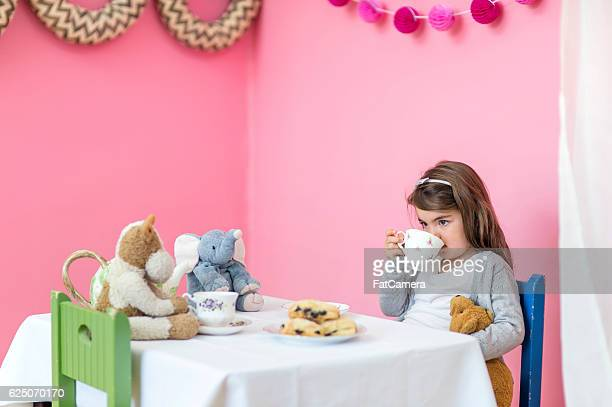 Young girl having a tea party with her stuffed animals