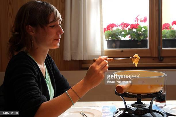 Young girl having cheese fondue.