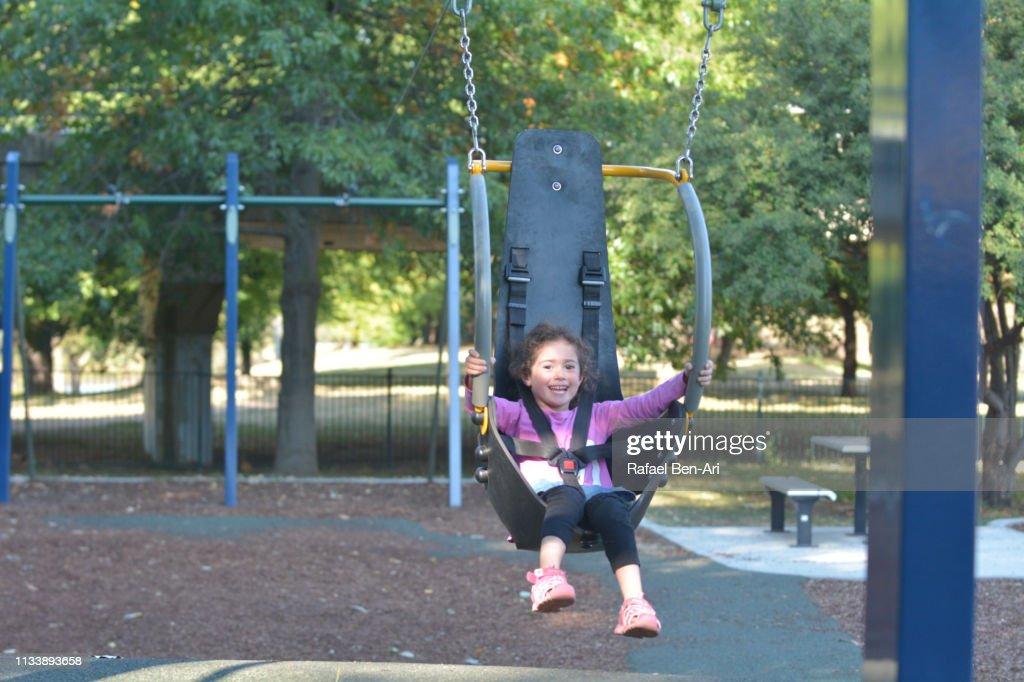 Young girl having fun on a flying fox swing : Stock Photo