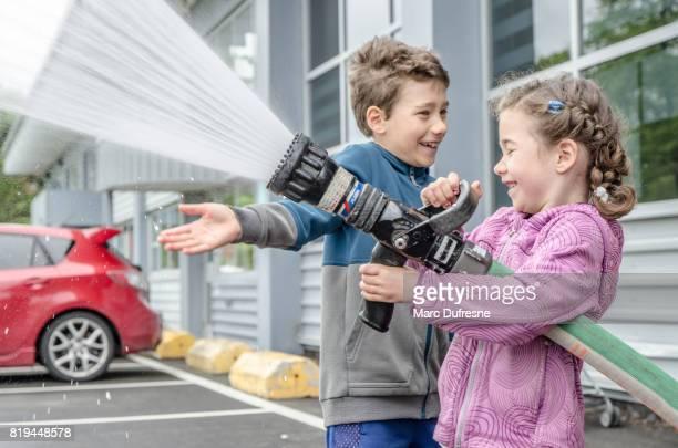 Junge Mädchen, die Spaß mit großen Feuerwehrschlauch während eines Besuchs in der Feuerwache