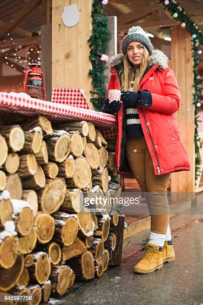 Junges Mädchen mit heißen Getränken am Weihnachtsmarkt