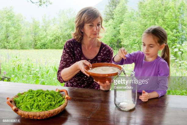 Young Girl Help Making Syrup Of Spruce Buds And Sugar