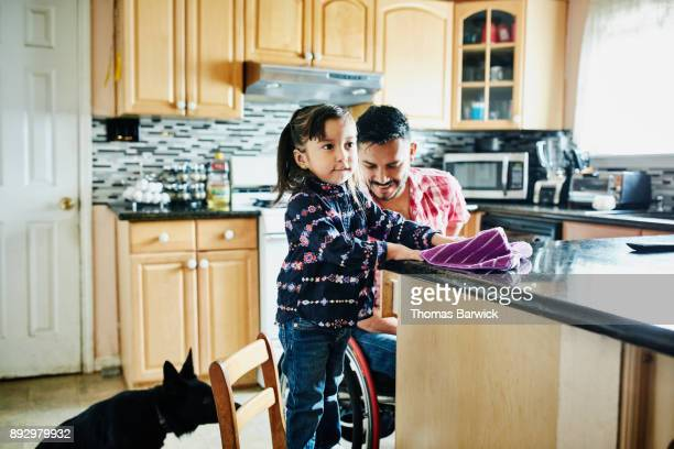 Young girl helping father in wheelchair clean kitchen in home