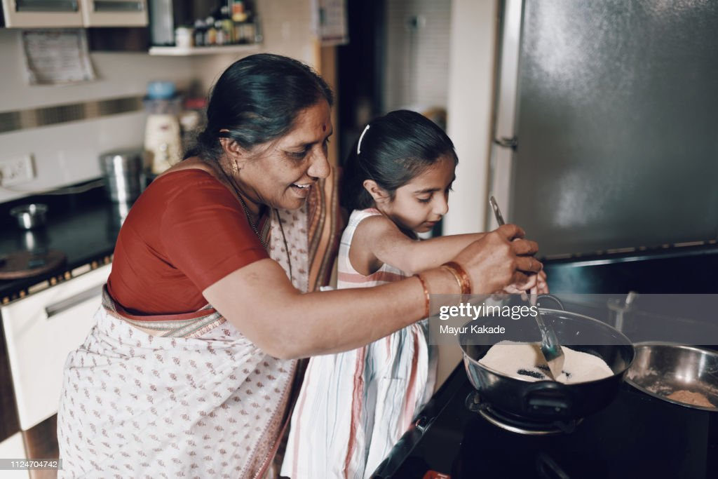 Young girl helping her grandmother while working in the kitchen : Stock Photo