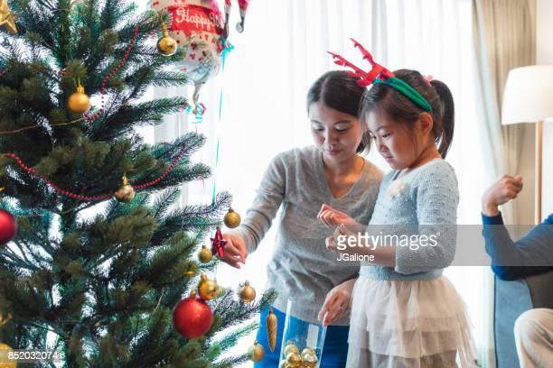 クリスマス ツリーを飾る彼女のお母さんを手伝って若い女の子